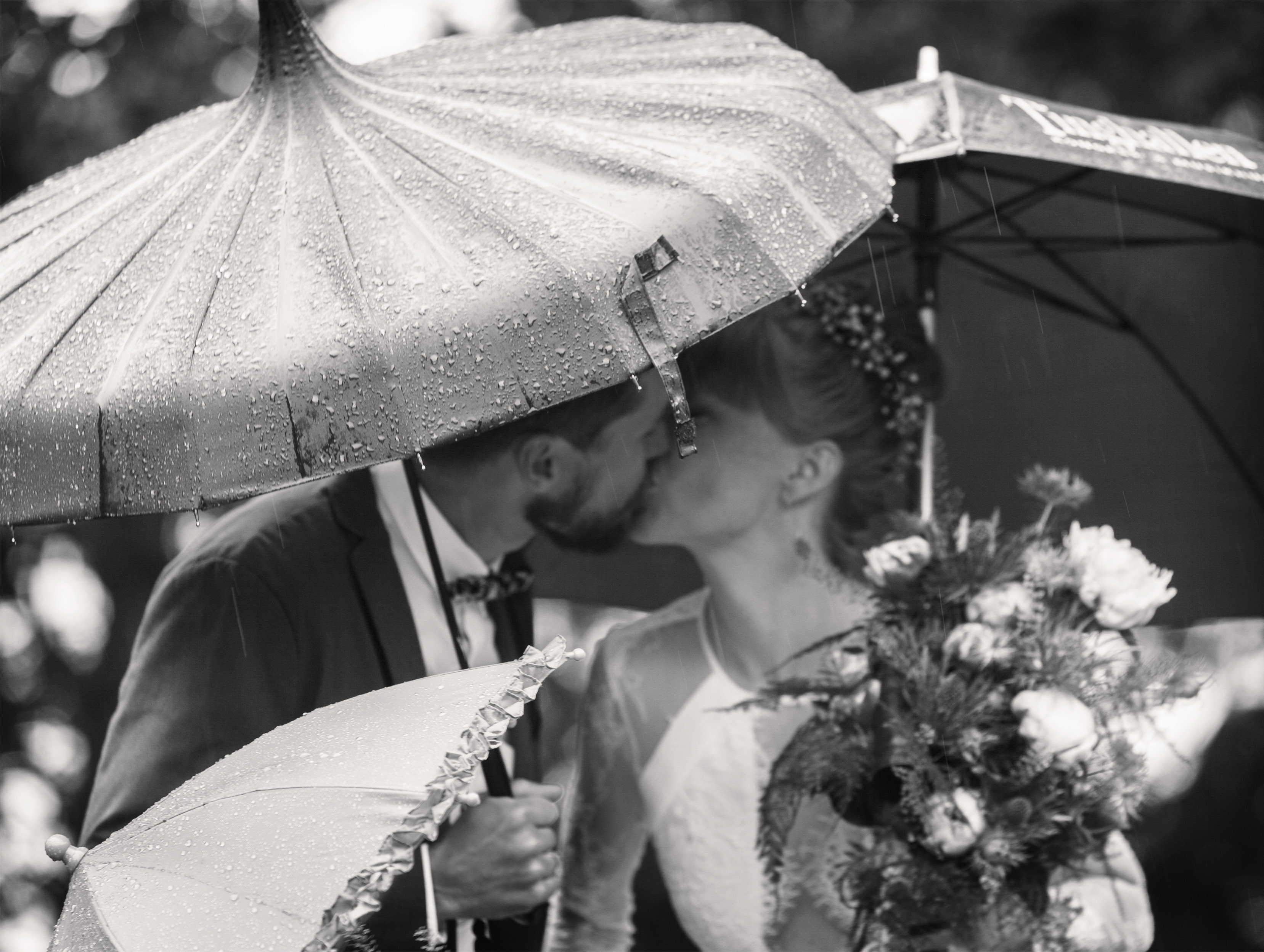 rain-wedding-kiss-flowers-umbrella-photo